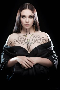 Emotional female actress with body painting posing on black background