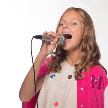 Emotional blonde girl in a pink jacket with a microphone