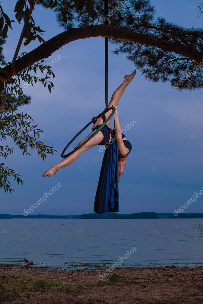 Girl performing acrobatic elements on the ring on the shore of the lake. Training aerial gymnastics