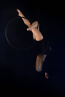 gymnast girl aerial acrobatics on t ring on background of blue smoke in dark