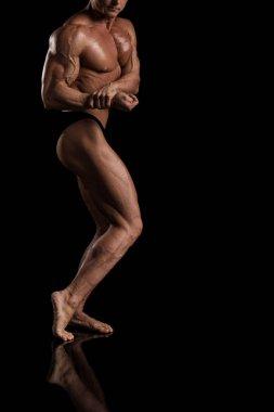 brutal man bodybuilder competitor on a black background