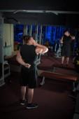 Mladý sportovec kulturista lodě a dělat sportovní cvičení v tělocvičně