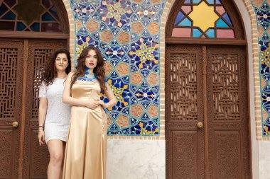 two young beautiful women in oriental dresses posing outdoors
