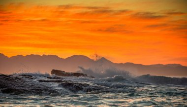 Seascape. Clouds in a red dawn sky, waves crashing with splashes against stones, silhouettes of mountains on the horizon. False bay. South Africa.