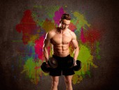 Strong guy with colorful paint wall and weight