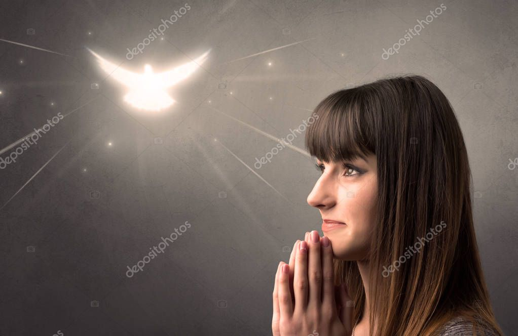 Young woman praying on a grey background with a sparkling bird above her stock vector