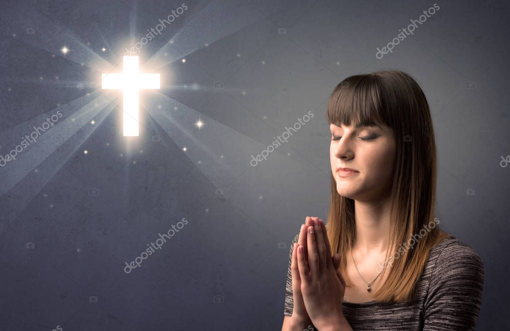 Young woman praying on a grey background with a shiny cross above her stock vector