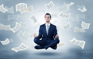 Young businessman meditating with documents and papers flying around him stock vector