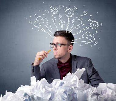 Young businessman sitting behind crumpled paper with drawings of gears and steam over his head stock vector