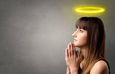 Young woman praying on a grey background with a shiny yellow halo above her head stock vector