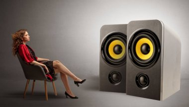 Young lady listening to big loudspeakers