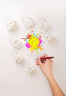 Female hand next to a few crumpled paper balls drawing a colorful lightbulb stock vector