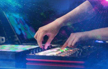 Hand mixing music on dj controller with party club colors around