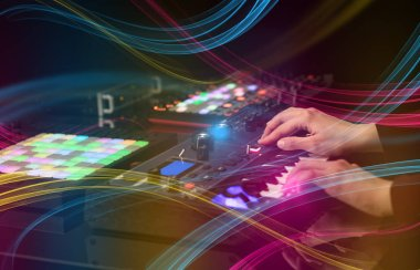 Hand mixing music on dj controller with colorful vibe concept