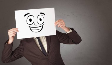 Young student holding a paper with laughing emoticon in front of his face stock vector