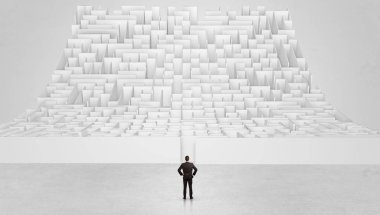 Small man standing in front of an infinity maze