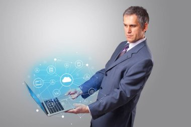 Man holding laptop with cloud based system concept