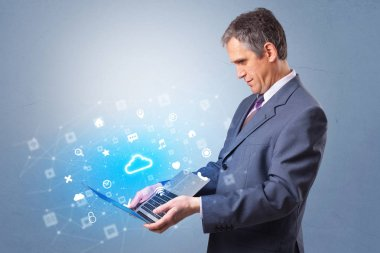 Man holding laptop with cloud based system notifications
