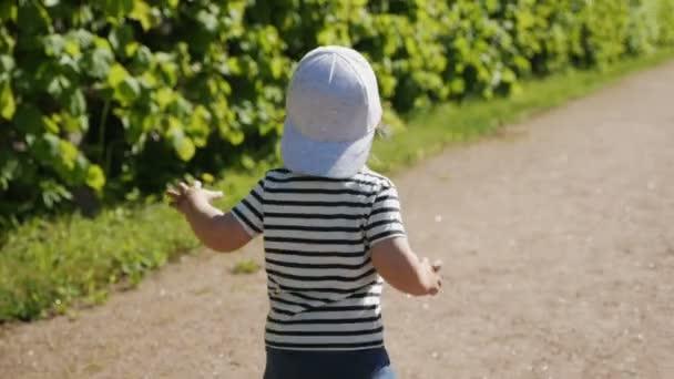 Junge in Mütze und T-Shirt läuft auf der Straße mit