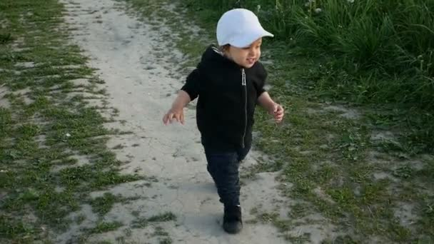 child in a jacket with a hood and a cap runs in the field along