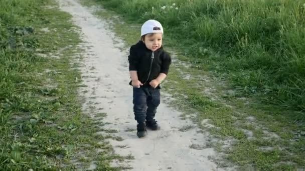 Kind in Jacke mit Kapuze und Mütze läuft im Feld mit