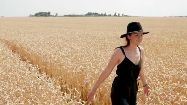 Žena v černých šatech a klobouk je na hřišti