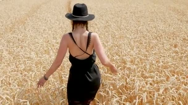 woman in a black dress and a hat is on the field