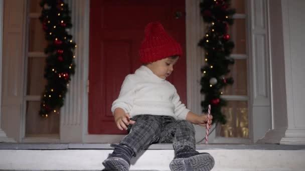 Kind steht in weißem Pullover und rotem Hut auf der Veranda im Schnee