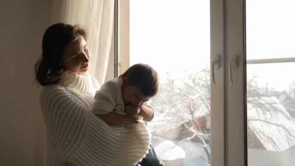 Máma a syn sedí na velké okno domu v zimě
