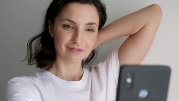 woman in a white t-shirt on a light wall makes a selfie