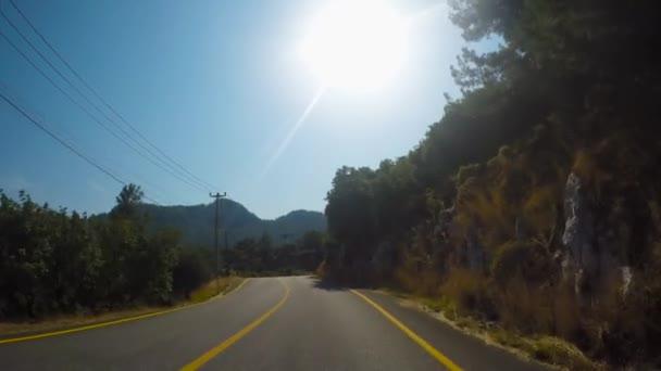 Auto fährt auf Bergwaldstraße mit Kurven im Sommer bei sonnigem Wetter