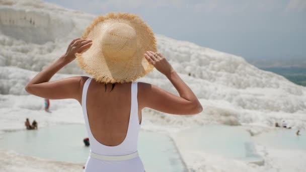 woman in a white swimsuit and a straw hat stands on a white mountain