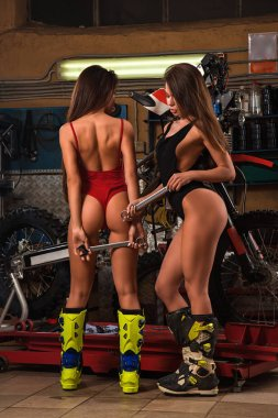 Twp sexy model girls in red lingerie posing with tools repairing motorcycle using tools in garage