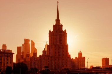 Hotel Ukraine at sunset, Moscow, Russia. It is a Stalinist skyscraper and landmark of Moscow. Sunny panorama of Moscow with old and modern tall buildings. Beautiful cityscape of Moscow in sun light.