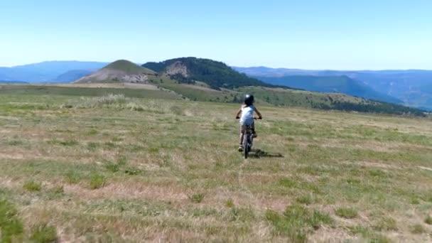 Malý chlapec na horském kole na koni přes francouzské hory