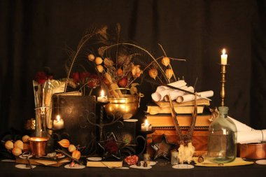Black Magic Spells. Wiccan spells and herbs. Still Live: Old oil lamps, antique books, dried rose buds, a burning candle in a copper bowl, medicine bottles, lavender, Pulsatilla pratensis on an antique background. Wicca background.