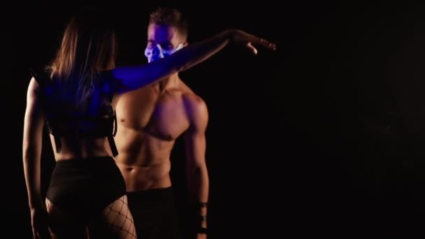 Muž a žena tanec v maskách lebka