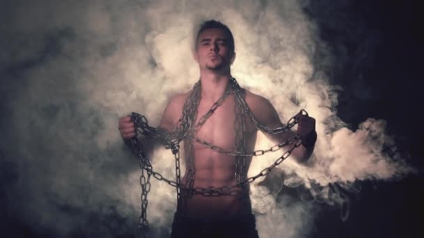 Man in Metal Chains in Smoke