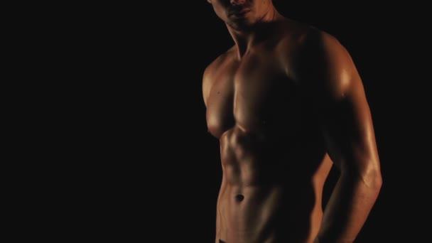 sexy Mann posiert auf schwarzem Hintergrund