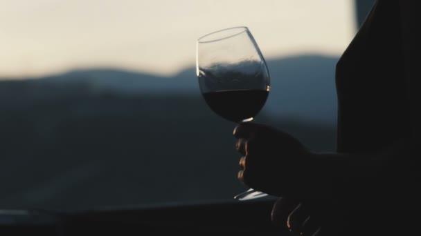 junge Frau trinkt Rotwein aus einem Glas und beobachtet den Sonnenuntergang