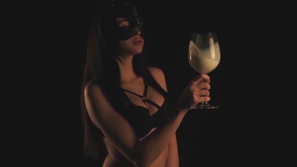 Girl in cat mask drinking milk in a glass