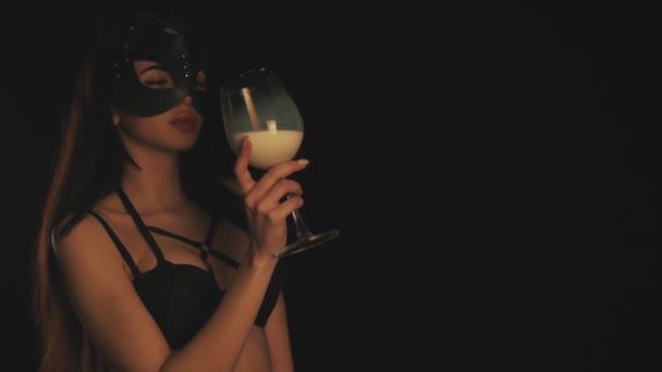 Mädchen in Katzenmaske trinkt Milch im Glas
