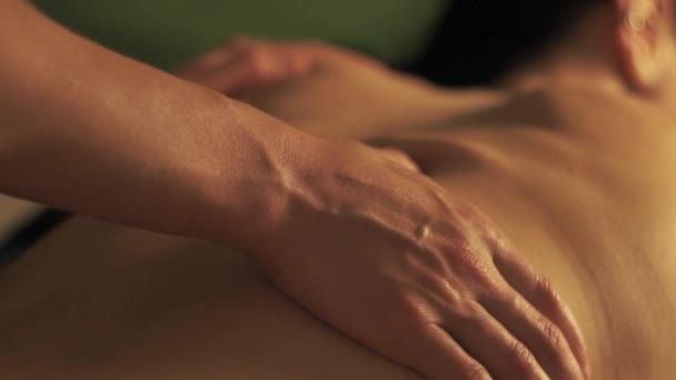Concept of massage. Beautiful young woman gets a relaxing massage