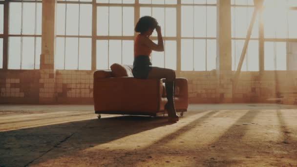 Nő ül egy piros szék a fény sugarai