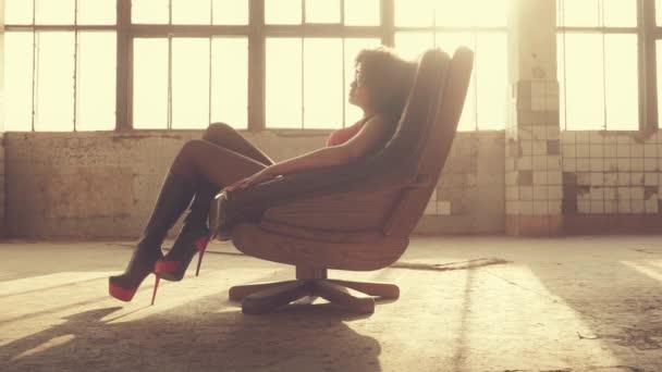Sexy žena sedí v křesle v paprscích světla