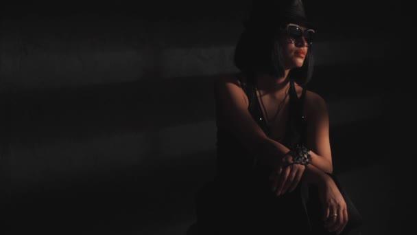 Žena v klobouku a skleničkách ve světle