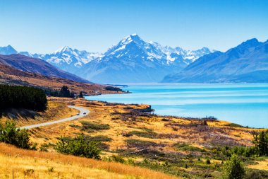 View of the majestic Aoraki Mount Cook with the road leading to Mount Cook Village. Taken during summer in New Zealand.