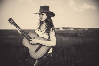 young woman in hat playing guitar at rural meadow background