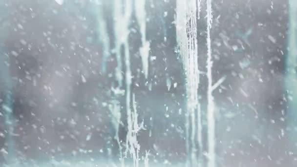 falling snowflakes at frozen winter season glass with frost patterns