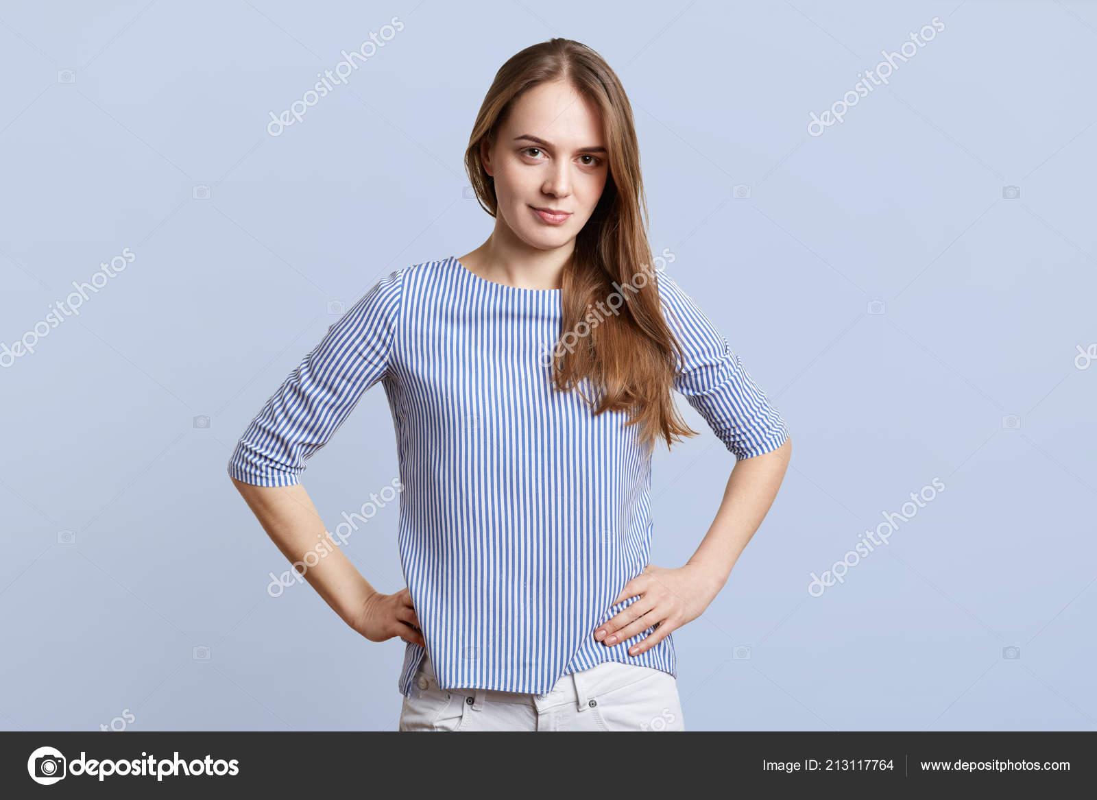 b9d3bceba0f0 Tiro horizontal de bastante femenina en ropa elegante mantiene las manos en  la cintura, mira con expressionn confiada y decidida en la cámara, ...